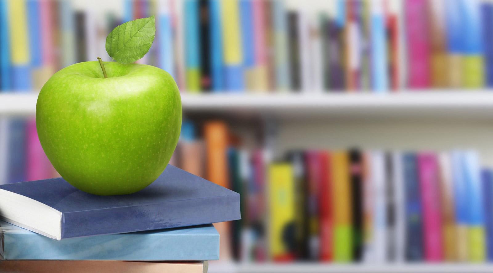 Libros y manzana en una biblioteca
